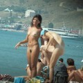 Couple of girls on busy nudist beach