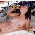 Nudist girls take a drink at the beach
