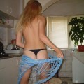 Young blond girl and her striptease  in kitchen