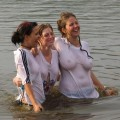 Funny girls on lake in wet shirts