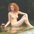 Nudist woman take a drink