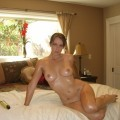 Naked girl lubricated with oil posing on bed