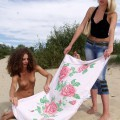 Two girls have fun at nudist beach
